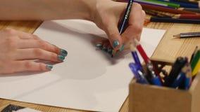 Het meisje trekt potloodschets op papier Sluit omhoog stock videobeelden