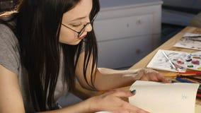 Het meisje trekt potloodschets op papier Sluit omhoog stock video
