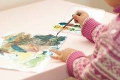 Het meisje trekt verven op een blad van document stock afbeeldingen