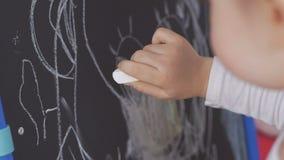 Het meisje trekt wit krijt op een tekenbord stock video