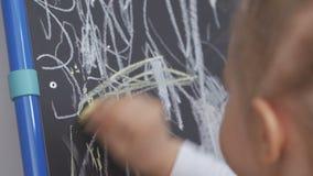 Het meisje trekt wit krijt op een tekenbord stock footage