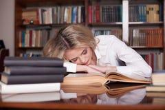 Het meisje trof voor de het boekslaap van de examenlezing voorbereidingen stock afbeelding