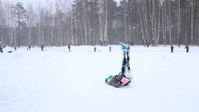 Het meisje tuimelt en doet eerst tuimelende pas tijdens sneeuwval bij de winter stock footage