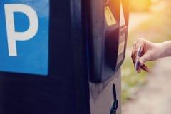 Het meisje typt de tekst met haar handen voor het opmaken van het kaartje voor het parkeren van de parkerenmachine en betaling vo stock foto