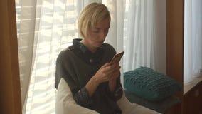 Het meisje typt een bericht in de telefoon stock videobeelden