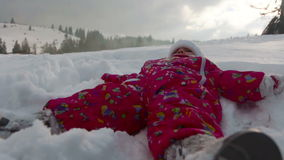 Het meisje valt op sneeuw en lacht stock footage