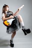 Het meisje van Cosplay in zwarte kleding met gitaar stock foto
