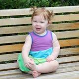 Het meisje van de één éénjarigebaby op een parkbank Royalty-vrije Stock Foto's
