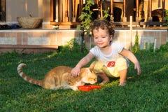 Het meisje van de Ailurophile leuke baby het houden van kat op gras stock afbeeldingen