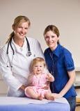 Het meisje van de arts, van de moeder en van de baby in artsenbureau Stock Fotografie