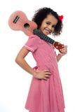 Het meisje van de Atttactiveschool met stuk speelgoed gitaar Stock Afbeeldingen