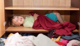 Het meisje van de baby is in de kast Stock Foto's