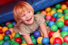 Het meisje van de baby en kleurrijke ballen Stock Foto's