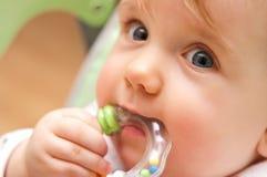 Het meisje van de baby het bijten stuk speelgoed Stock Afbeeldingen