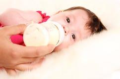 Het meisje van de baby het drinken melk van fles Stock Foto's