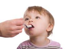 Het meisje van de baby het eten stock afbeelding