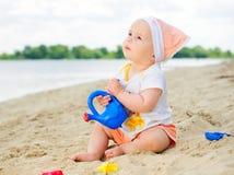 Het meisje van de baby het spelen op het strand met zand. royalty-vrije stock afbeeldingen