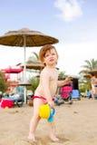 Het meisje van de baby het spelen op het zandstrand Stock Foto's