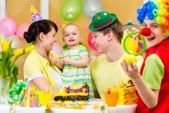 Het vieren van de baby eerste verjaardag met ouders en clown Royalty-vrije Stock Foto