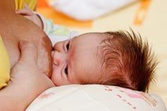 Het meisje van de baby het zuigen bij de borst van haar moeder stock afbeeldingen