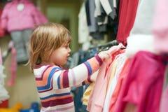 Het meisje van de baby kiest kleren bij winkel Stock Foto