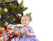 Het meisje van de baby maakt een wens onder Kerstboom Royalty-vrije Stock Foto
