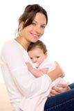 Het meisje van de baby met fopspeenomhelzing wordt ontspannen in moederwapens dat Royalty-vrije Stock Foto's