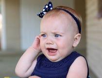 Het meisje van de baby met oorpijn stock foto