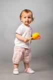 Het meisje van de baby met oranje maraca. Royalty-vrije Stock Foto's