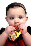 Het meisje van de baby met stuk speelgoed in mond Royalty-vrije Stock Foto's