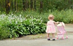 Het meisje van de baby met wandelwagen royalty-vrije stock afbeeldingen