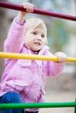 Het meisje van de baby op de speelplaats van het kind in de lentetijd Stock Foto's