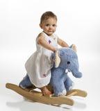 Het meisje van de baby op het schommelen olifant Stock Foto's
