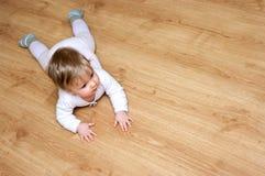 Het meisje van de baby op houten vloer stock fotografie