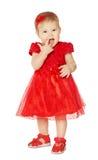 Het meisje van de baby in rode kleding Het gelukkige Jonge geitje in de Kleren van de Maniervakantie zuigt Vinger in Mond Geïsole royalty-vrije stock afbeelding