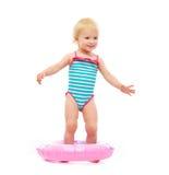 Het meisje van de baby in zwempak dat zich in opblaasbare ring bevindt Stock Fotografie