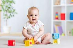 Het meisje van de babypeuter het spelen kleurenspeelgoed thuis of kinderdagverblijf Royalty-vrije Stock Fotografie
