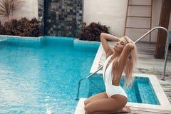 Het meisje van het de bikiniblonde van de luxereis met sexy lichaam in het witte swimwear stellen door zwembad bij luxueuze villa stock foto's