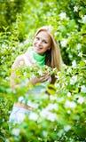 Het meisje van de blonde in de tuin op een zonnige dag Stock Afbeeldingen