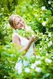 Het meisje van de blonde in de tuin op een zonnige dag Royalty-vrije Stock Afbeeldingen