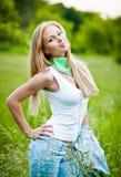 Het meisje van de blonde in de tuin op een zonnige dag Stock Foto