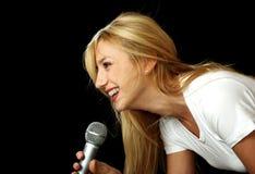 Het meisje van de blonde het zingen karaoke Stock Afbeeldingen