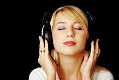 Het meisje van de blonde in hoofdtelefoons met ogen Stock Foto