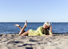 Het meisje van de blonde ligt dichtbij het overzees op zijn knieën Royalty-vrije Stock Foto
