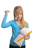 Het meisje van de blonde lost een wiskundig thuiswerk op Stock Afbeeldingen