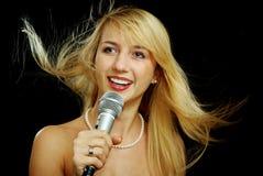 Het meisje van de blonde met naakte schouders die karaoke zingen Stock Afbeelding