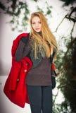 Het meisje van de blonde met rode laag in de wintersneeuw Stock Afbeelding