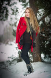 Het meisje van de blonde met rode laag in de wintersneeuw Stock Foto's