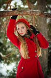 Het meisje van de blonde met rode laag in de wintersneeuw Stock Foto