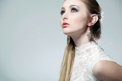 Het meisje van de blonde op witte close-up als achtergrond. Stock Foto's